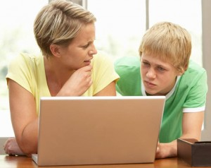Mother And Teenage Son Using Laptop At Home